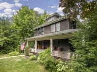 Brown Adirondack Home With Covered Porch