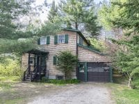 Exterior Of Adirondack Home With Green Trim