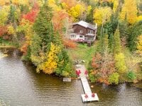 Aerial Of Chalet On Mirror Lake With Long Dock During The Fall
