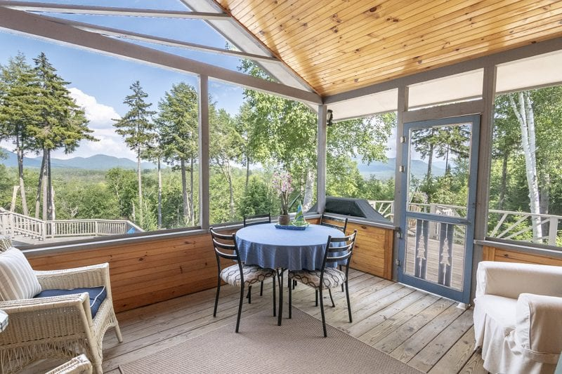 Screened Porch With Table And View Of The Lake