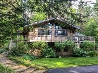 Brown Adirondack Chalet With Stone Path To Door