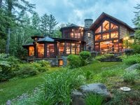 Exterior From Mirror Lake Side Of Custom Adirondack Home With Many Windows Facing The Lake