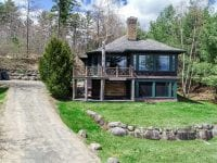 Aerial Of Brown Adirondack Home With Driveway