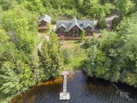 Aerial Of Exterior Of Large Home On Rainbow Lake With Dock