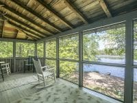 Screened Porch With Chair Overlooking Beach On Rainbow Lake