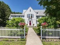 Exterior Of White Colonial Style Home With Pink Flowers Out Front