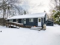 Blue Ranch Style Home During The Winter