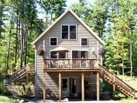 Exterior Of Grey Chalet With Stairs To The Deck