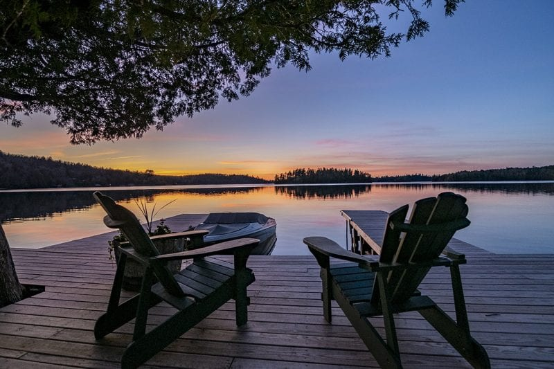 Dock At Sunset With Two Chairs And Boat