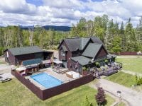 Aerial Of Brown House With Pool and Mountains In Background