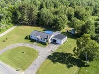 Aerial Of Ranch Style Home With Round About Driveway, Garage & Pool