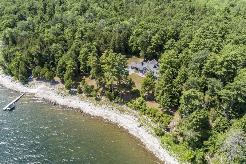 Aerial Of Waterfront And Exterior Of Large Blue House