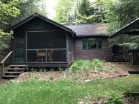 Exterior Of Brown Cabin With Screened Porch