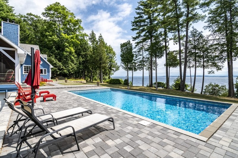 Patio With Lounge Chairs, Pool, Yard & View Of the Lake