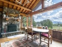 Screened Porch With Stone Fireplace, Dining Table And Golf Course Views