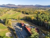 Aerial Exterior Of The Inn With Golf Course & Mountains