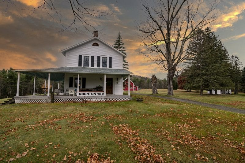 Exterior Of White Farmhouse During Sunset