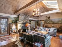 Great Room With Two Couches, Vaulted Ceiling & Door Way To Enclosed Porch