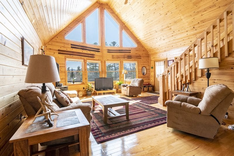 Living Room With Hardwood Floors, Vaulted Ceiling & Large Windows That Look Out To The Mountains